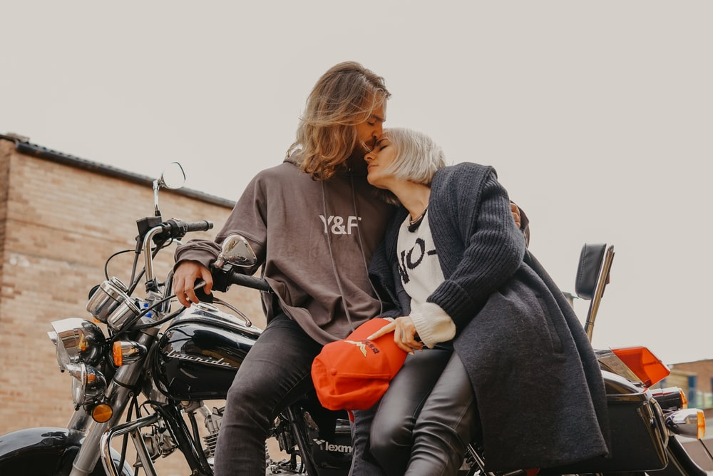 man kissing woman's forehead while sitting on motorcycle