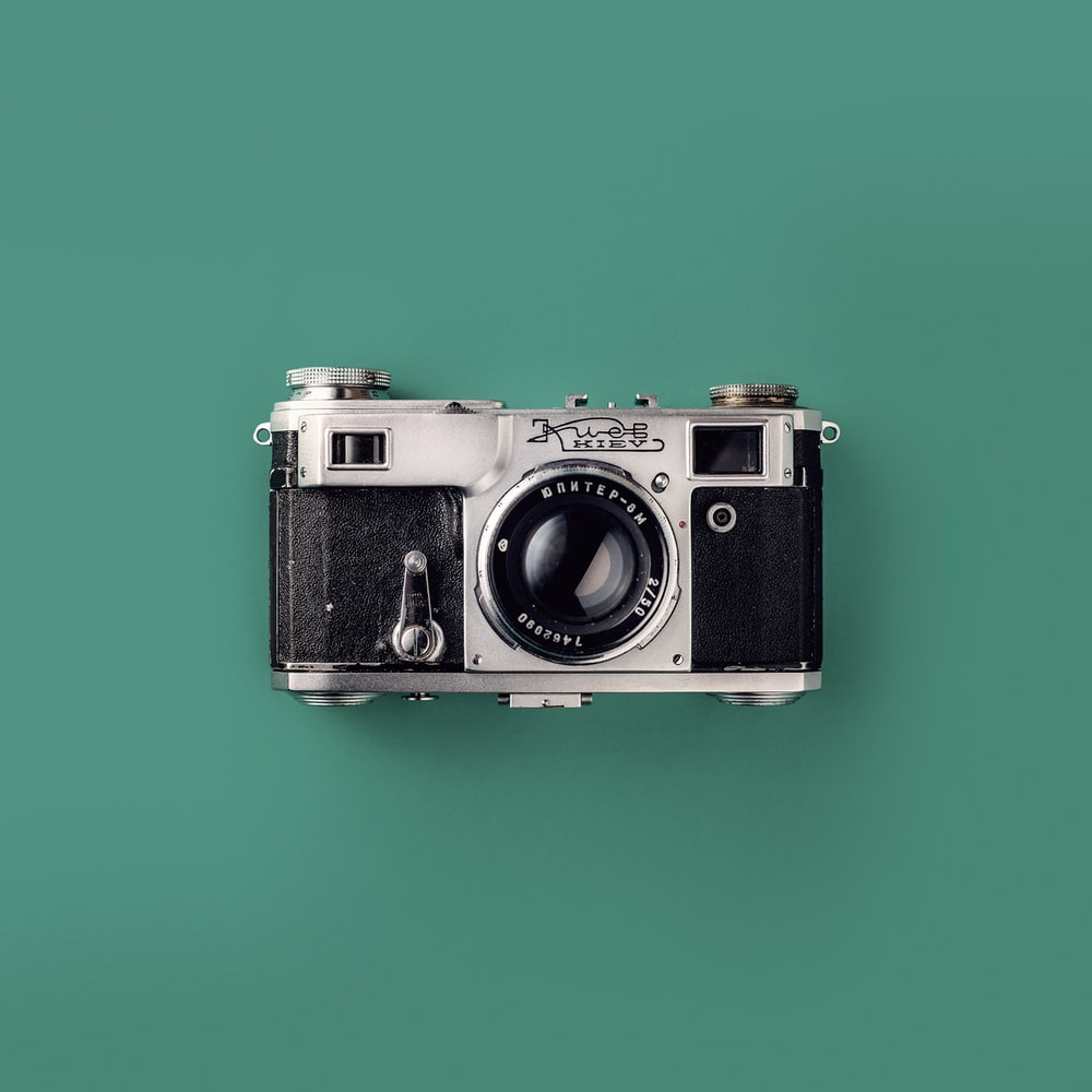 silver SLR camera on teal background