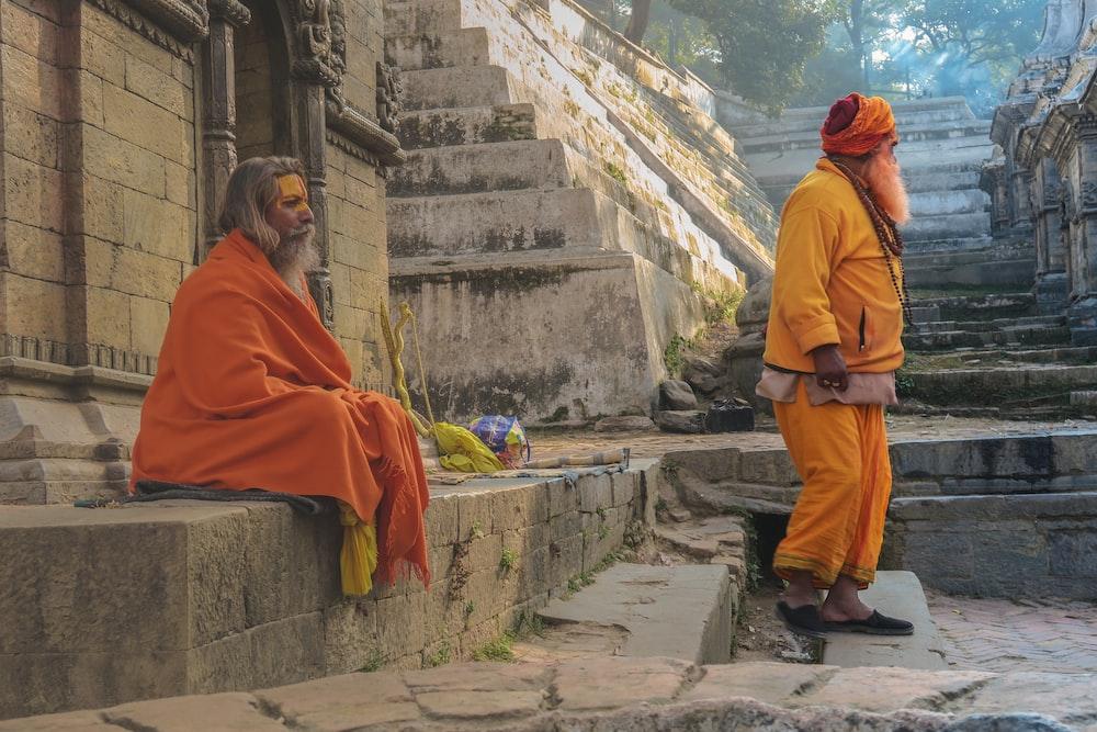 man wearing orange robe meditate