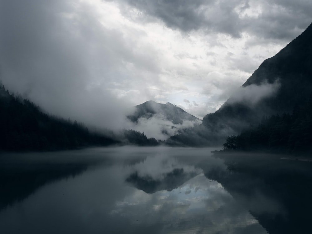 calm body of water near mountains