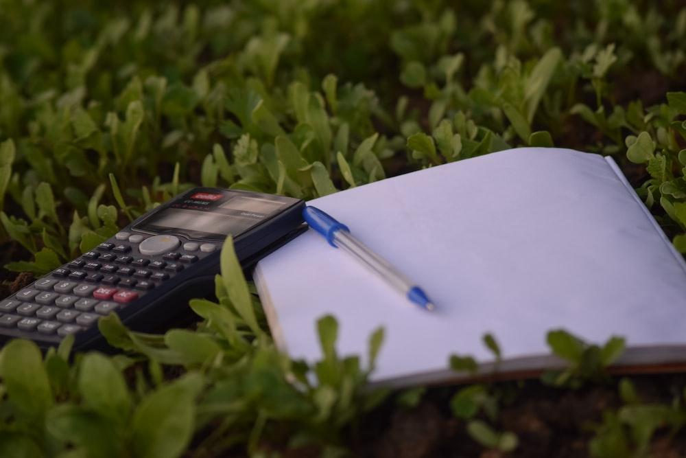 blue ballpoint pen on paper beside calculator