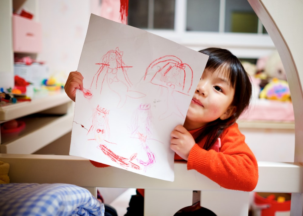 girl holding paper with drawing