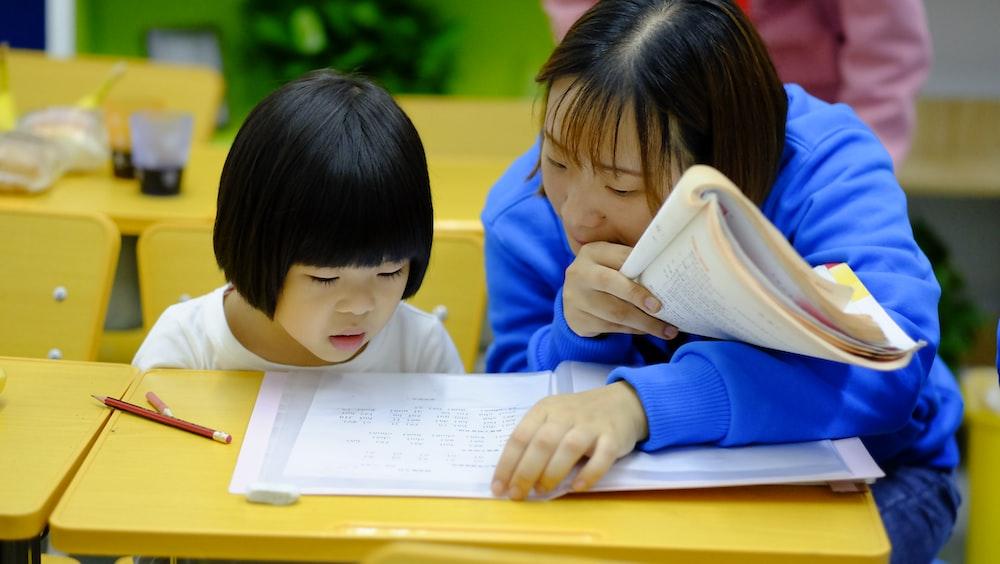 woman teaching girl