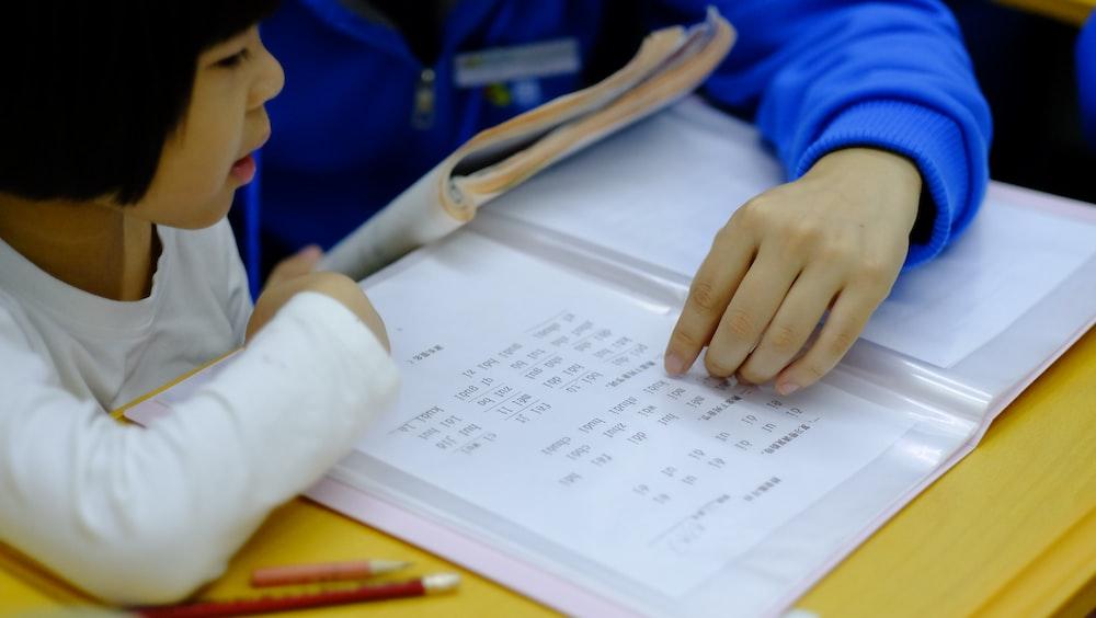 person teaching girl using book