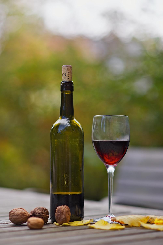 wine bottle beside wine glass on brown wooden surface