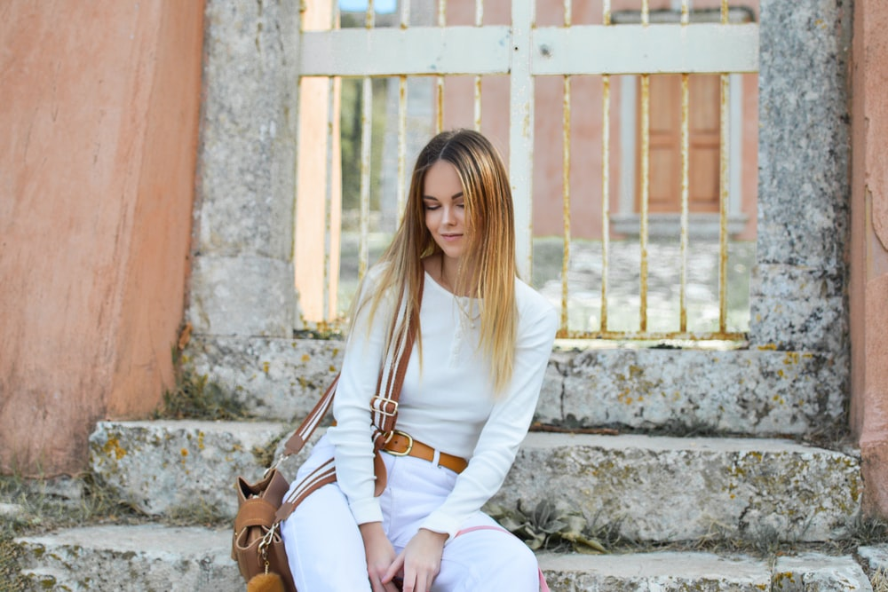 woman sitting on stair near gate
