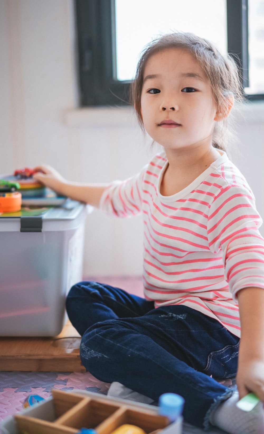 girl sitting on floor beside toys