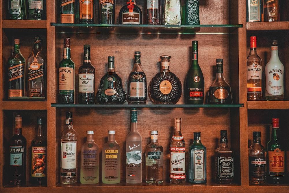 assorted liquor on brown wooden shelf