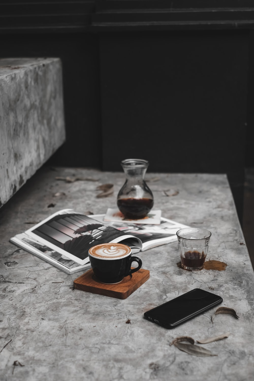 cup of rosetta art latte beside smartphone