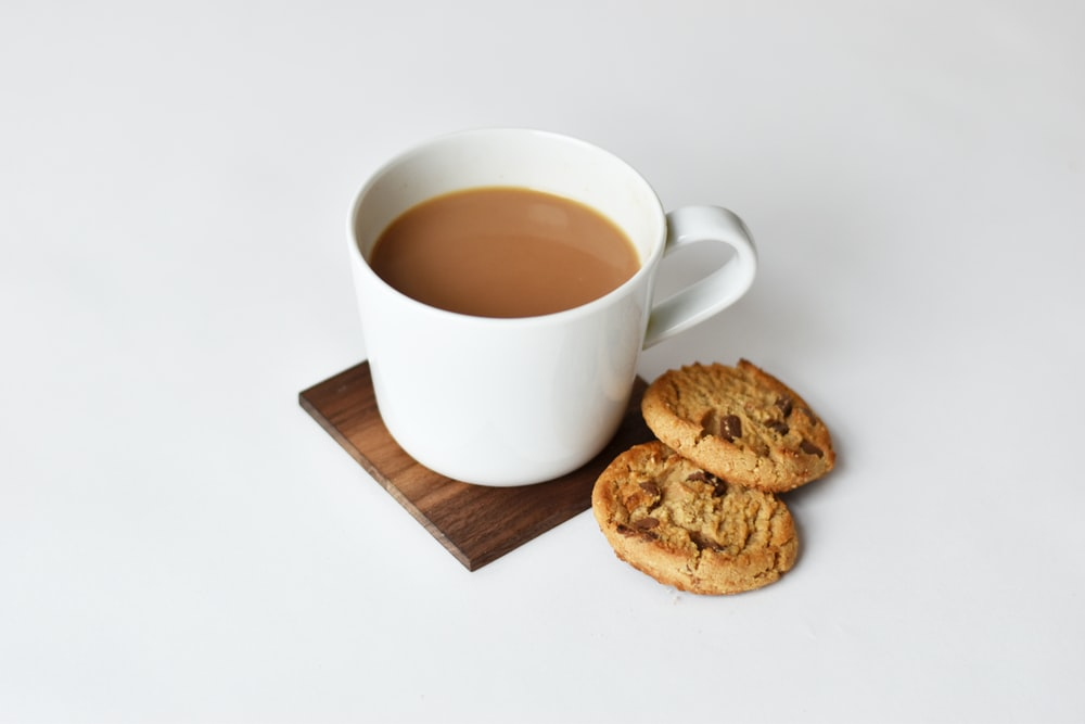mug with coffee and two cookies on brown coaster