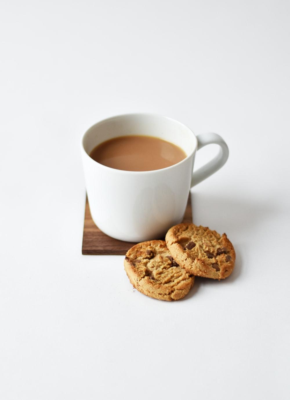 white ceramic coffee mug beside cookies