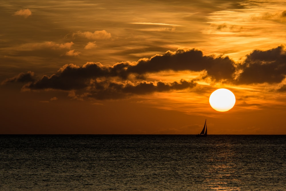 silhouette of sailboat on sea during golden hour