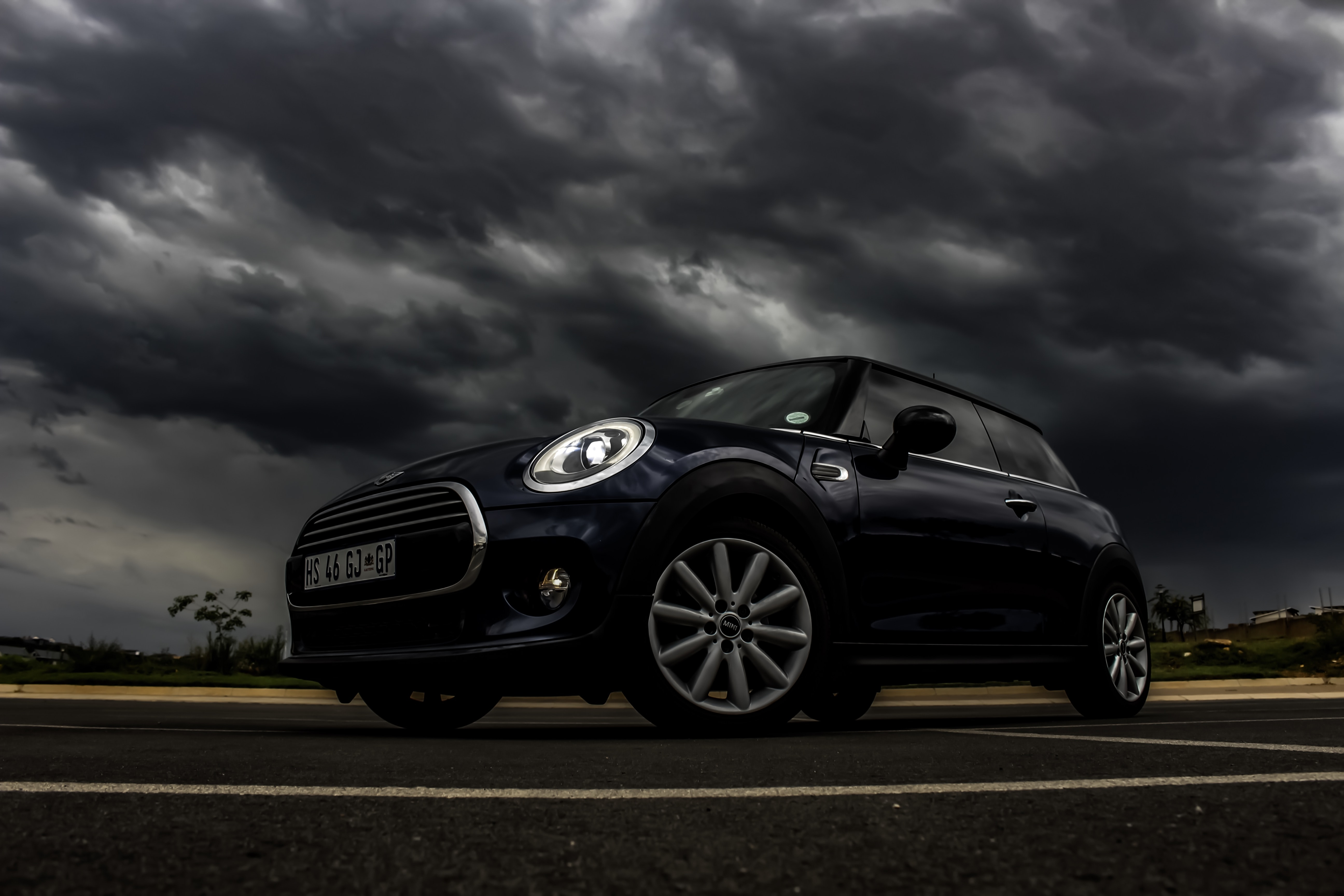 black Mini Cooper 3-door hatchback on road under cloudy daytime