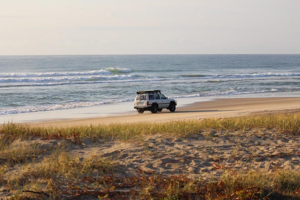 white vehicle beside seashore during daytime