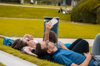 man and women lying on green grass taking photo