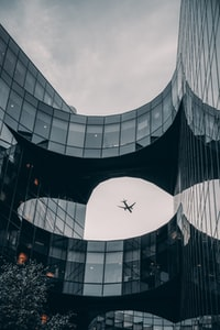 airplane above glass building during day