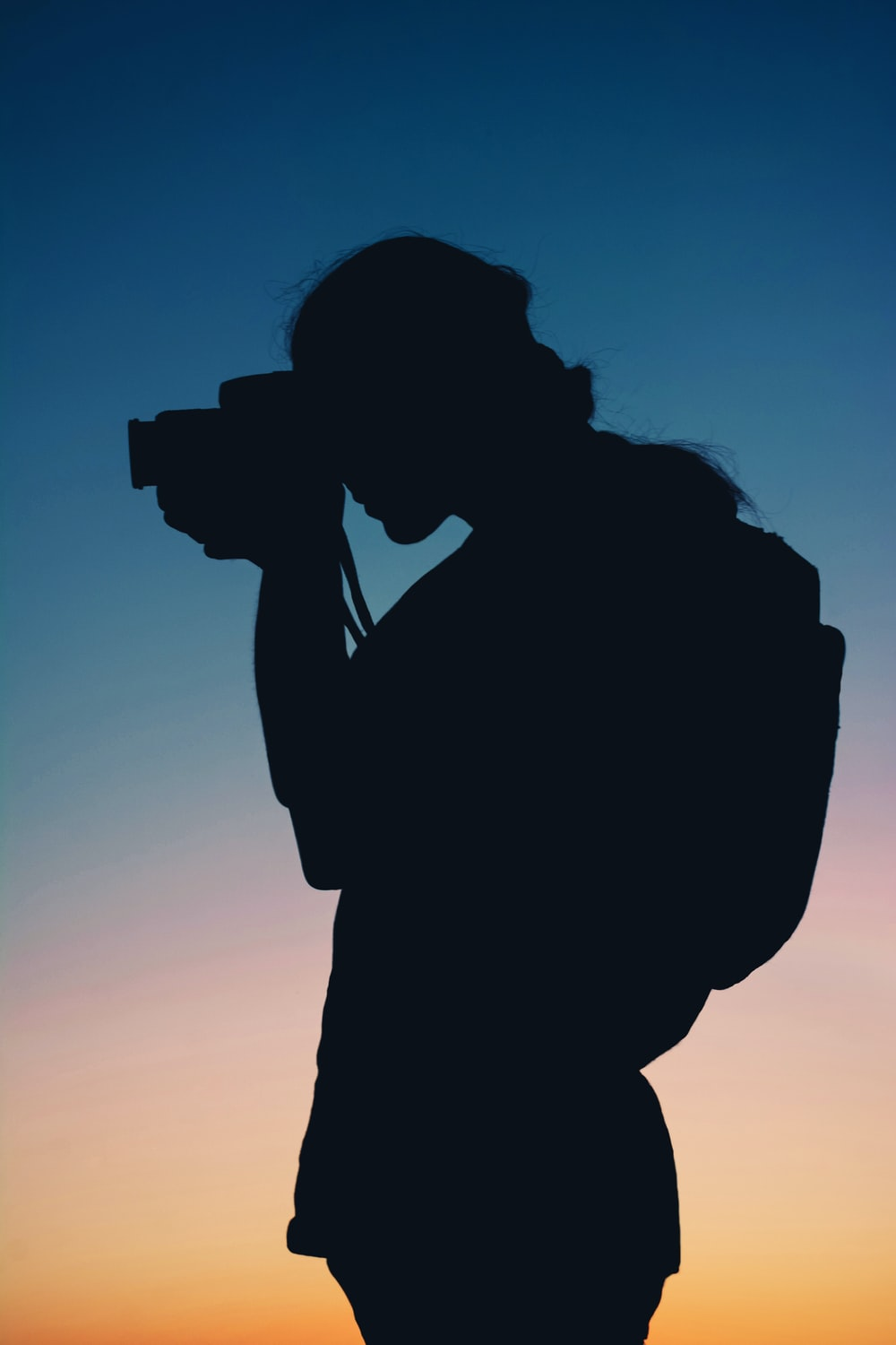 silhouette of person using camera