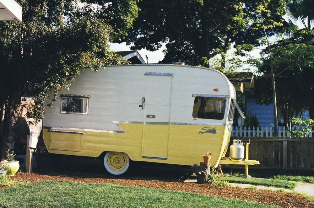 white and yellow travel trailer parked beside fence