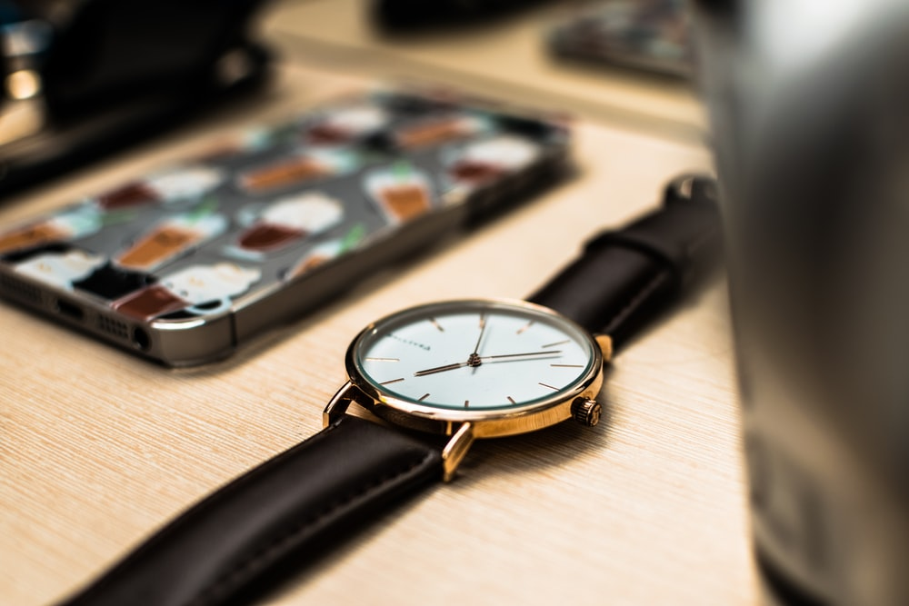 round white and gold-colored analog watch with black leather band on wooden surface