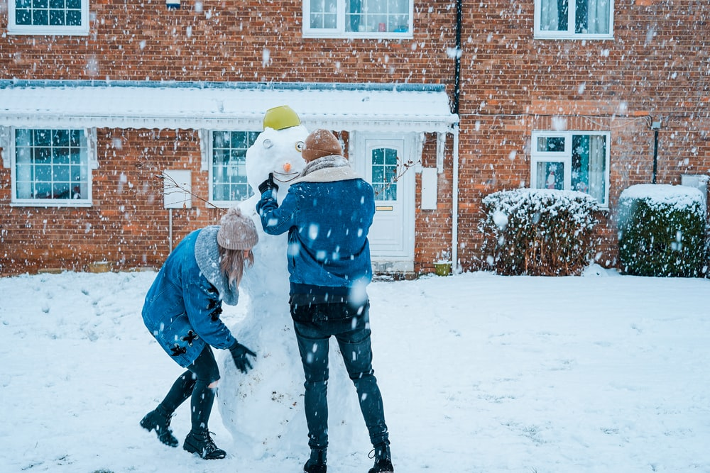 couple building snowman during winter