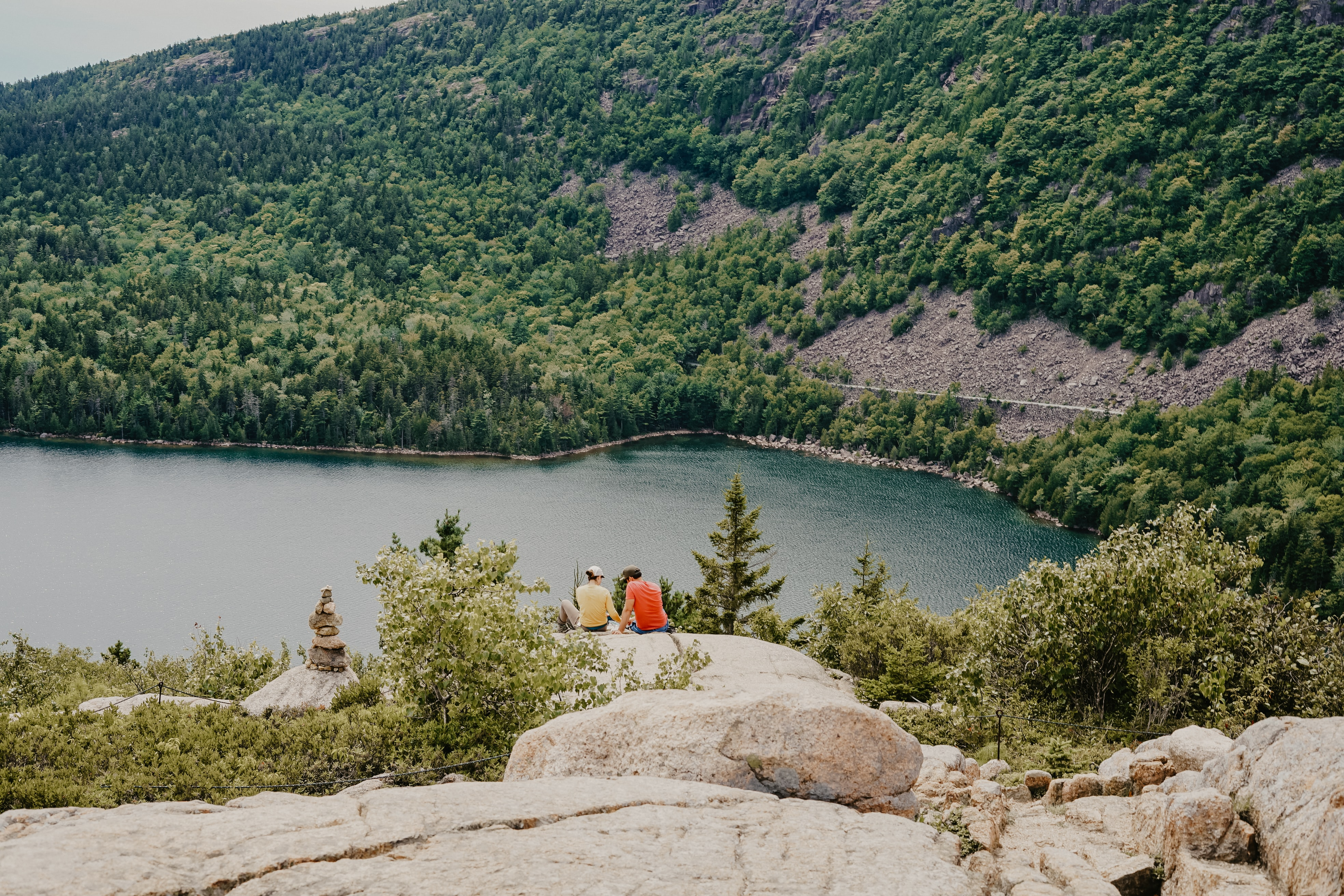 two person sitting on gray rock