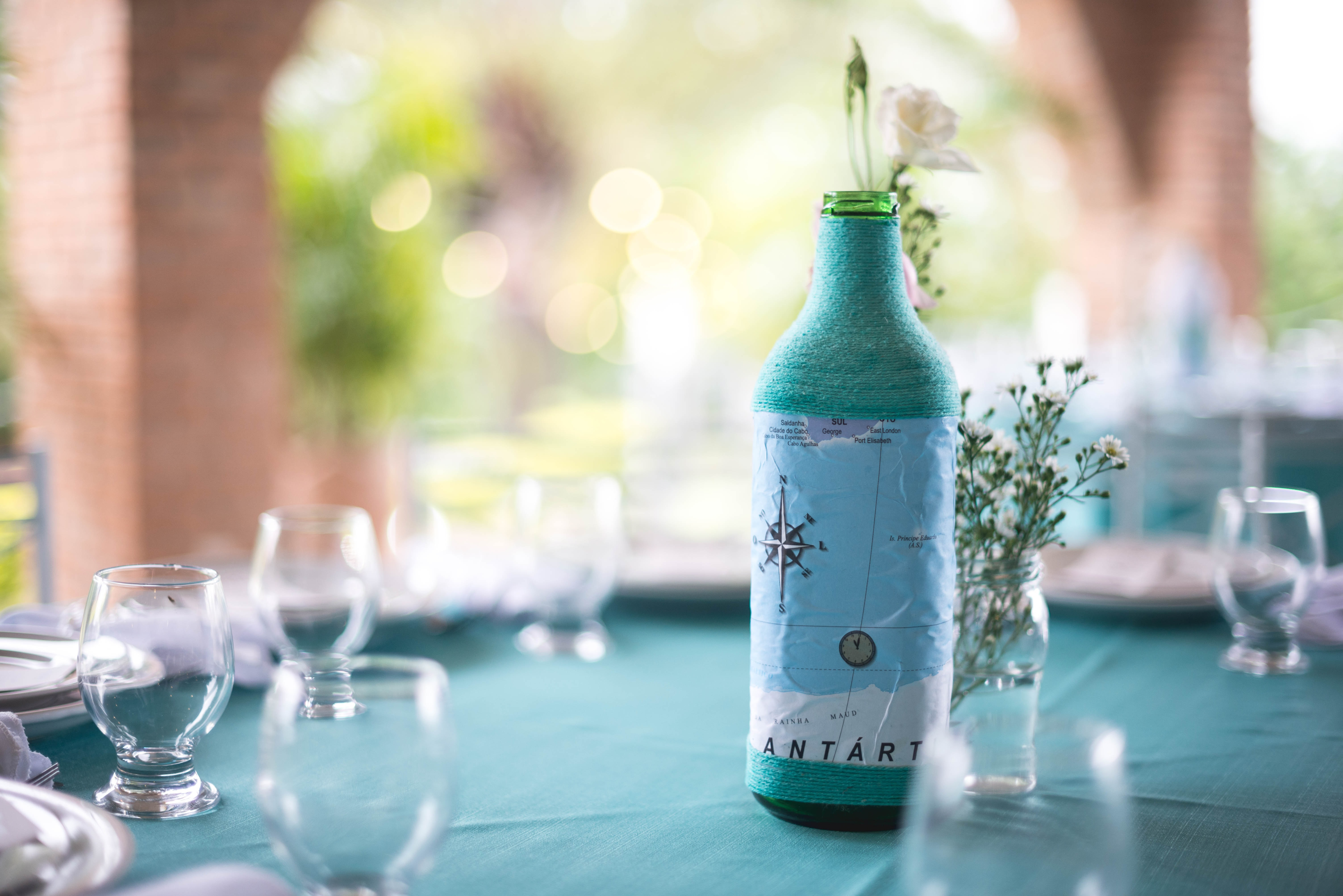 teal bottle in the middle of wine glasses