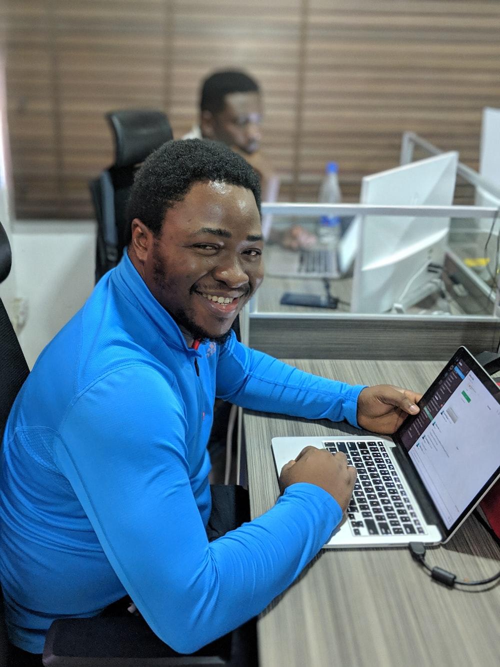 smiling man using laptop computer