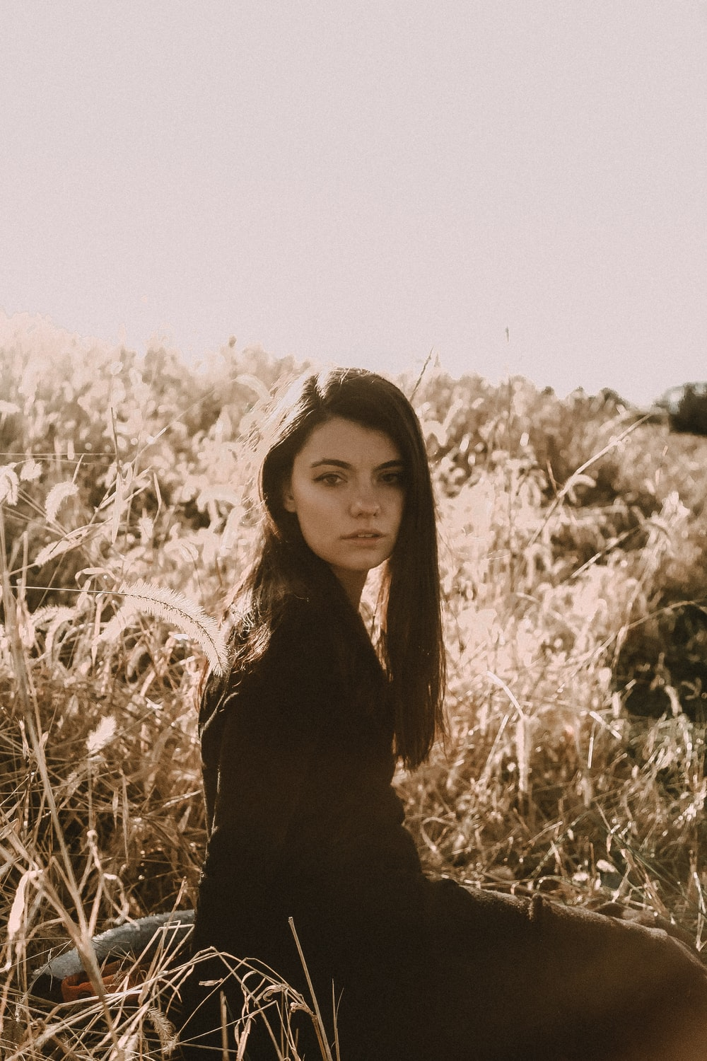 sepia photography of woman in long-leafed grass