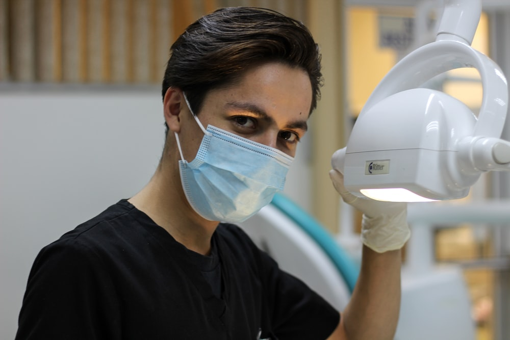 man with mask holding dental glass
