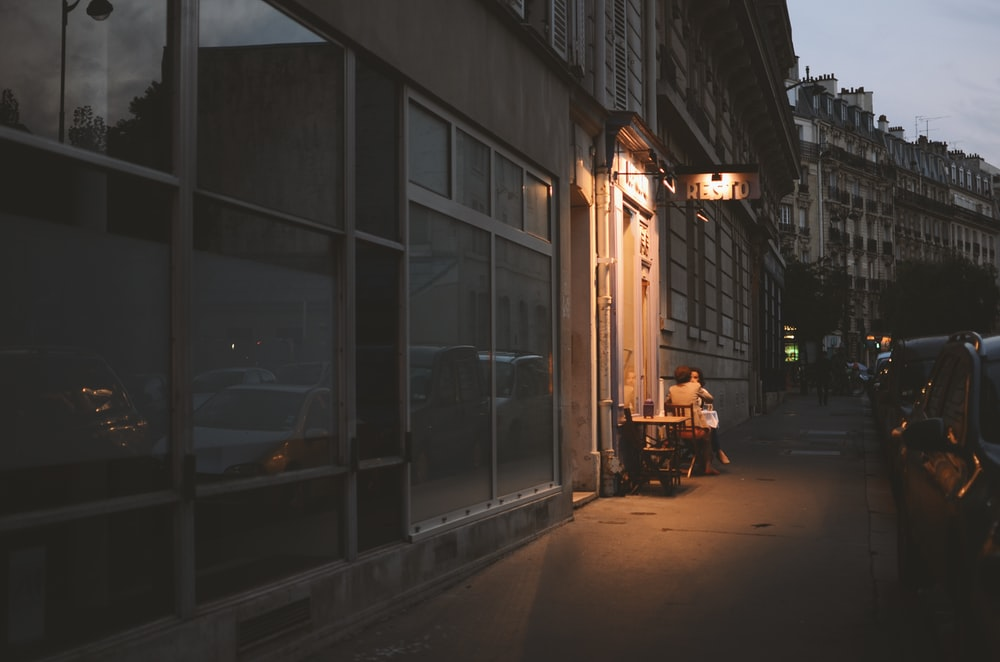 vehicles parked beside buildings at nighttime