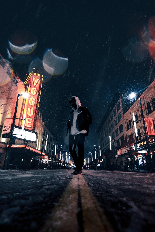 man standing on road between buildings
