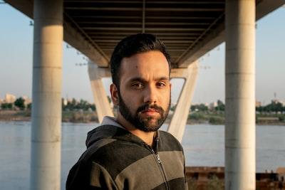 man standing under bridge iranian teams background