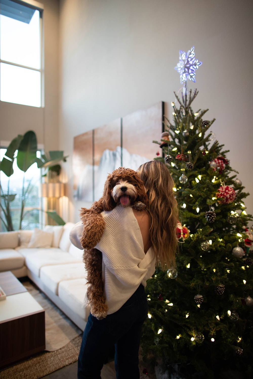 woman carrying dog beside Christmas tree