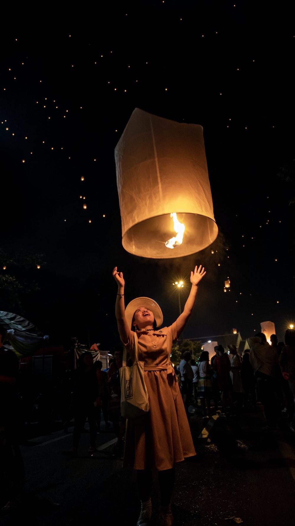 woman in brown dress holds sky lantern
