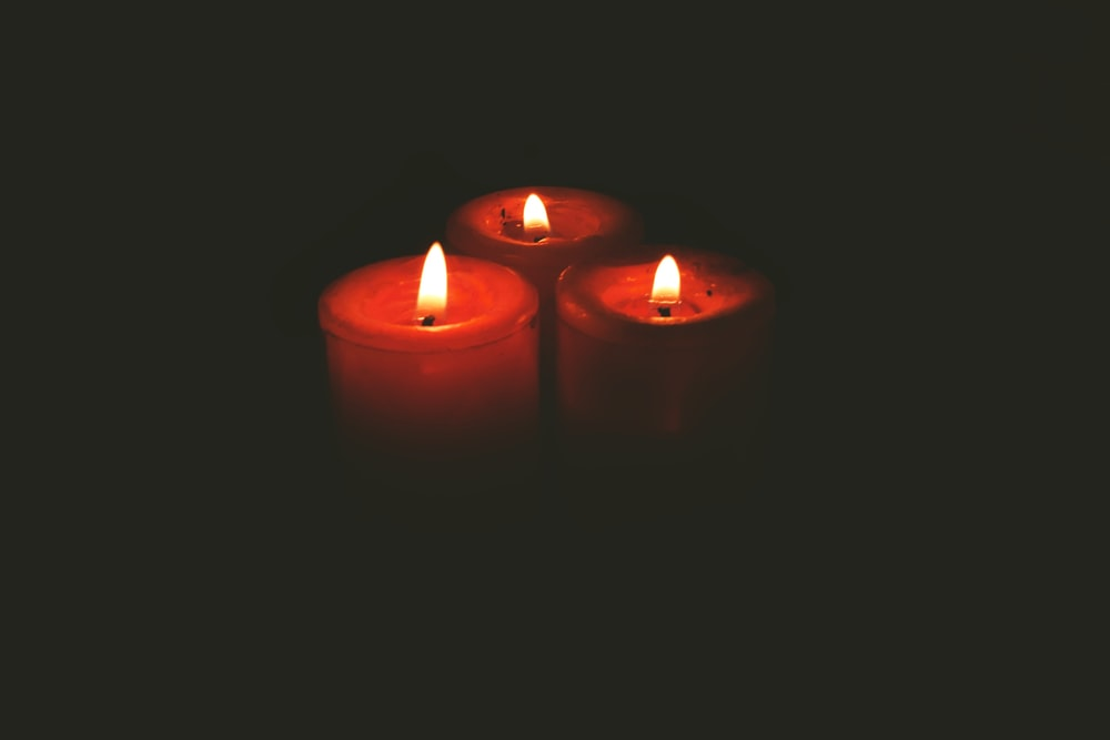 three red lit pillar candles