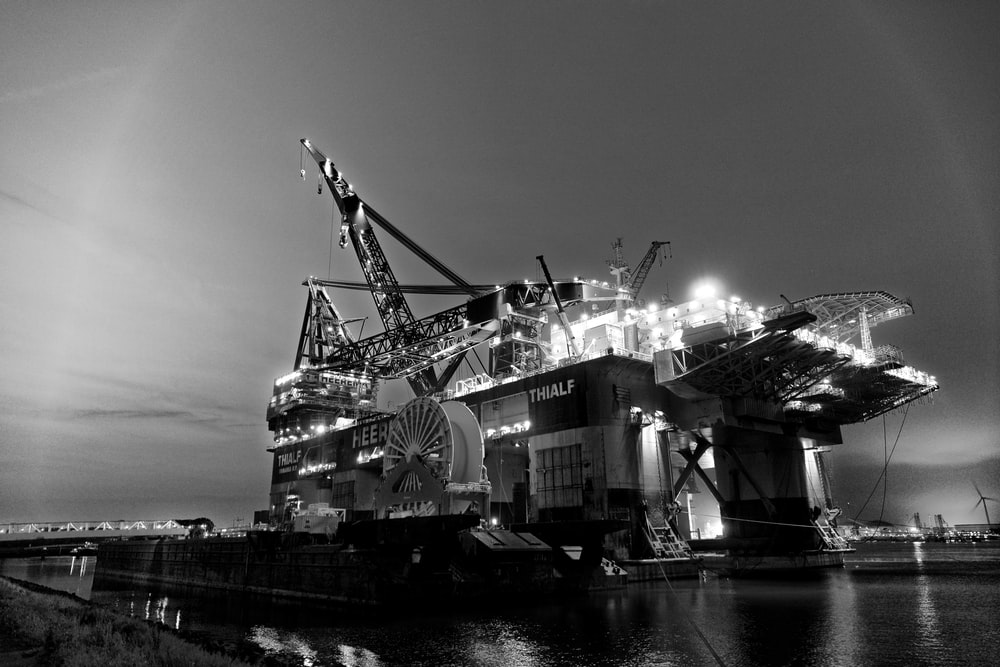 grayscale photography of oil rig