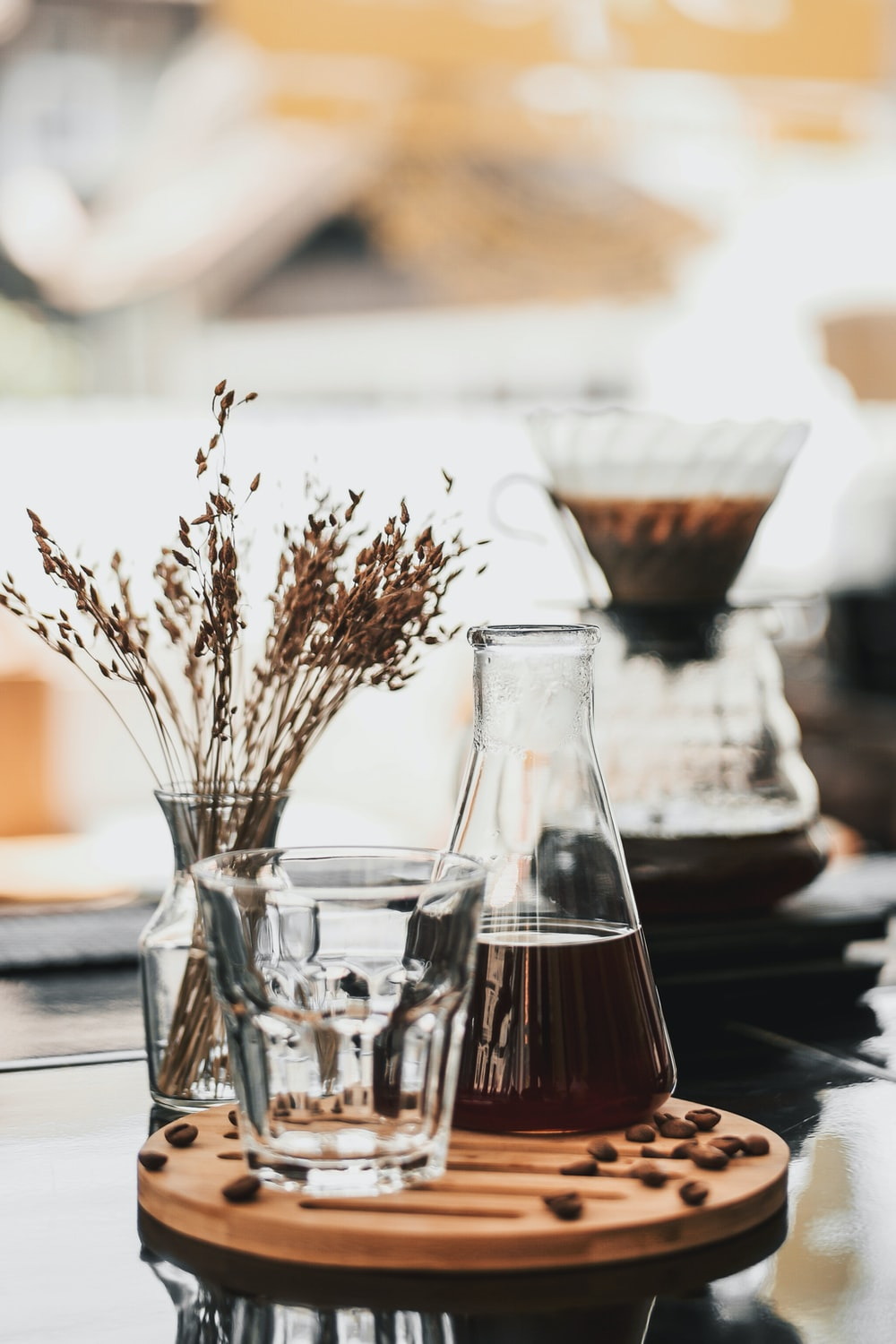 drinking glass beside glass flask and vase