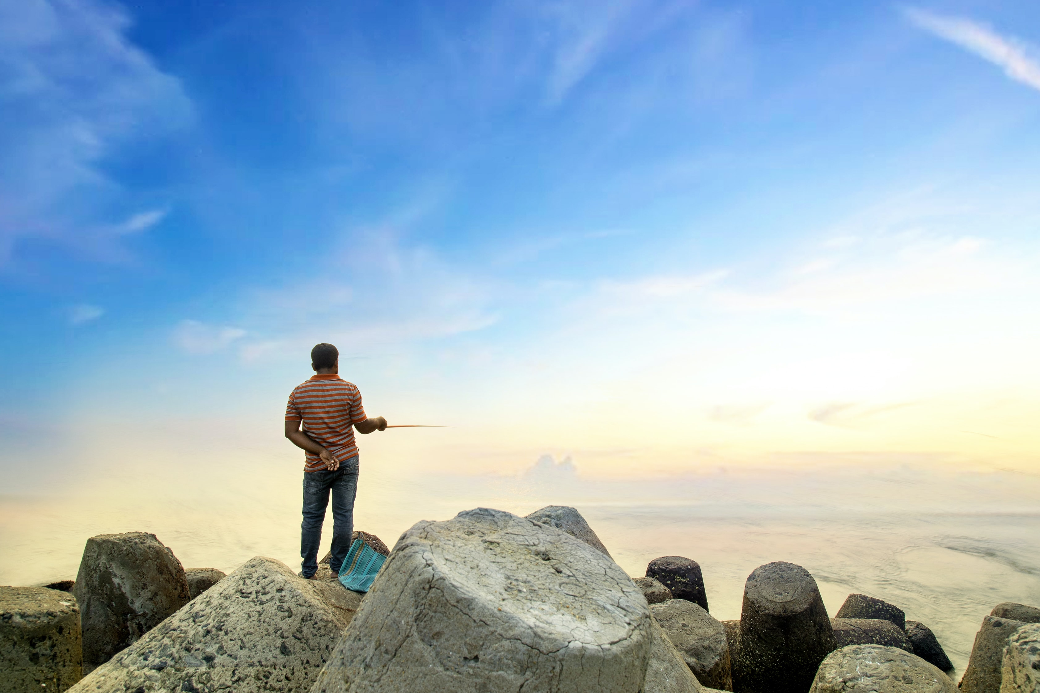 woman standing on big rocks overlooking body of water