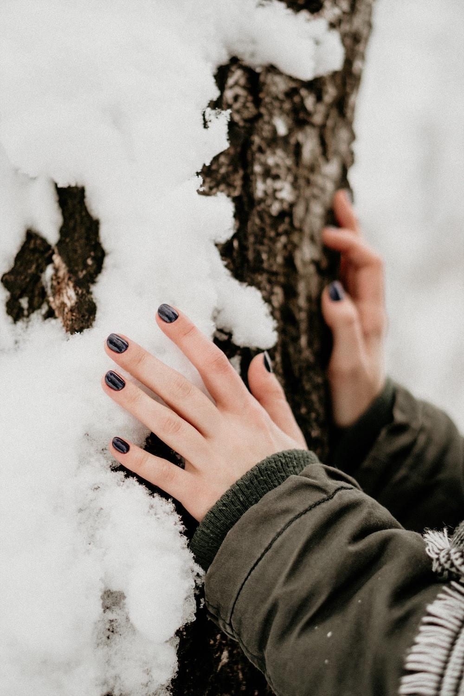 person touching gray stone