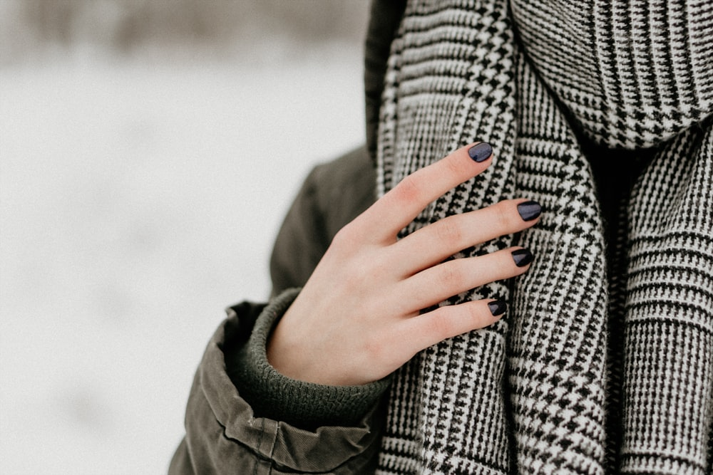 selective focus photography of person wearing black and white houndstooth scarf