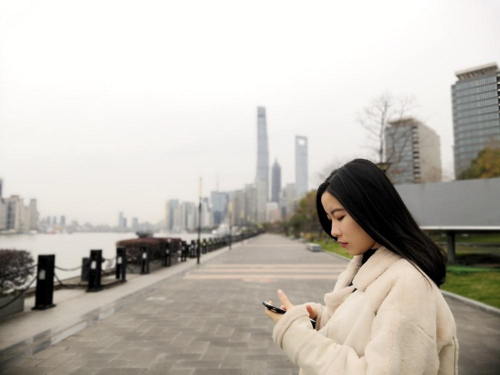 woman wearing fleece jacket using smartphone