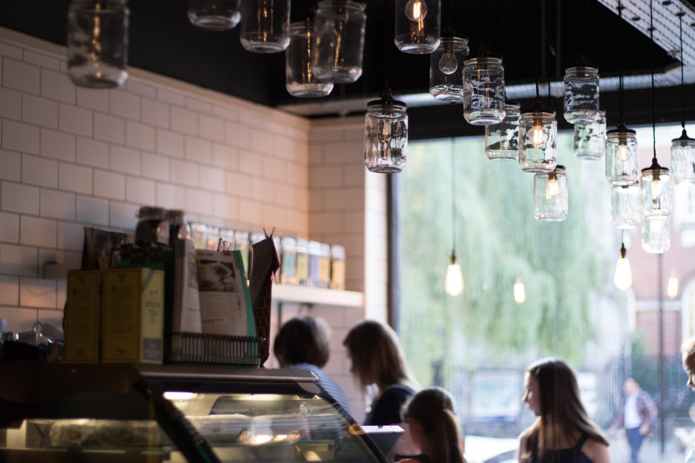 people inside restaurant with Mason jar pendant lamps