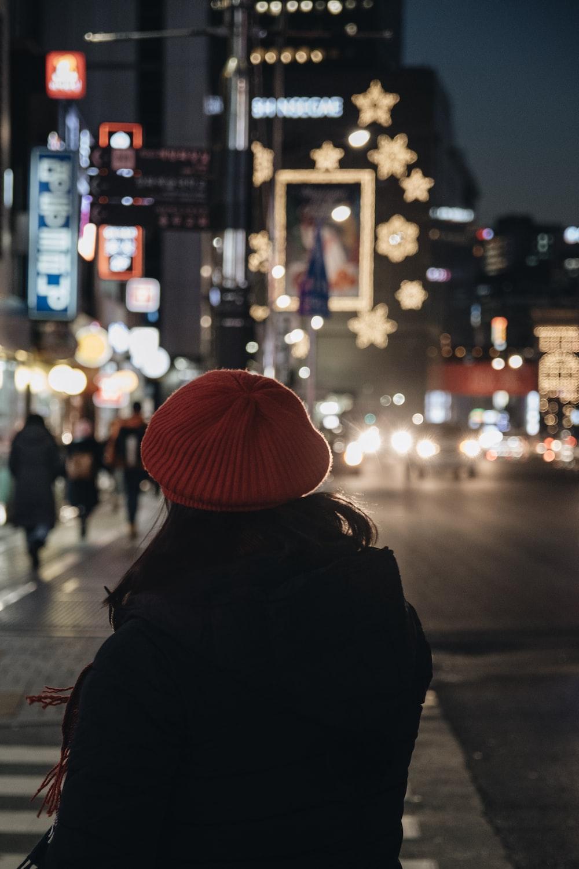 woman standing on pedestrian lane at night