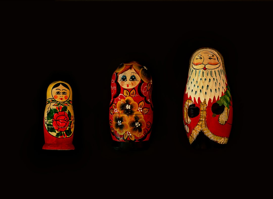 traditional Russian stacking dolls and one done to be an American Santa stacking doll on a black background in ascending order.