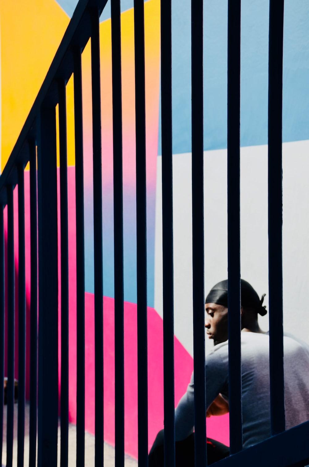 man sitting beside railing