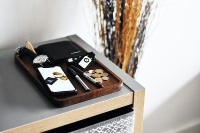 watch, smartphone and wallet on brown wooden tray