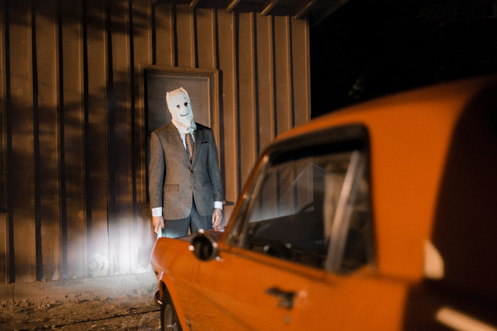 man with mask in front of car