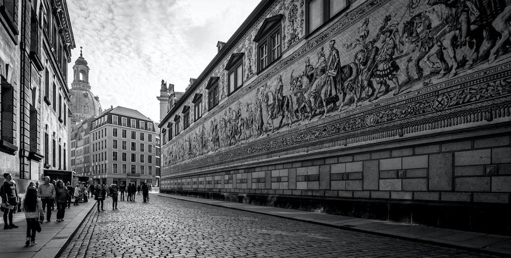 people walking by concrete wall