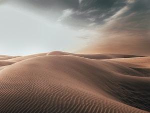 sand dunes at desert under grey cloudy sky