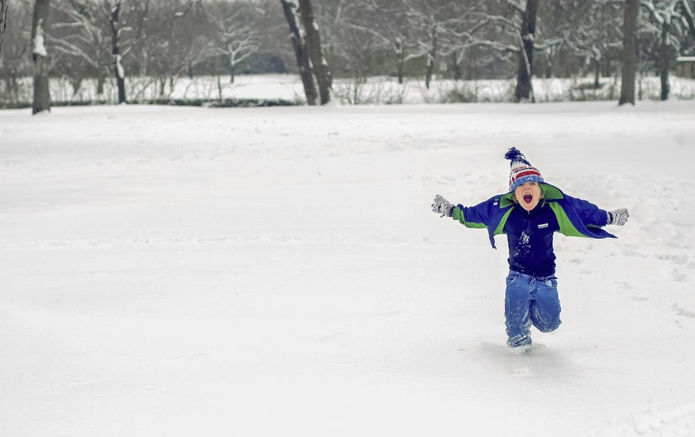 boy running on snow while opening his mouth
